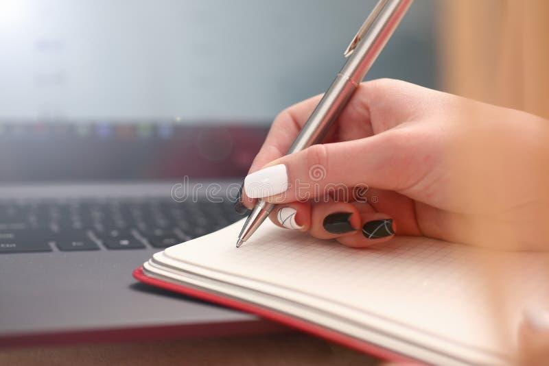 O estudo da mulher redige duramente para baixo a informa??o ao caderno fotografia de stock royalty free