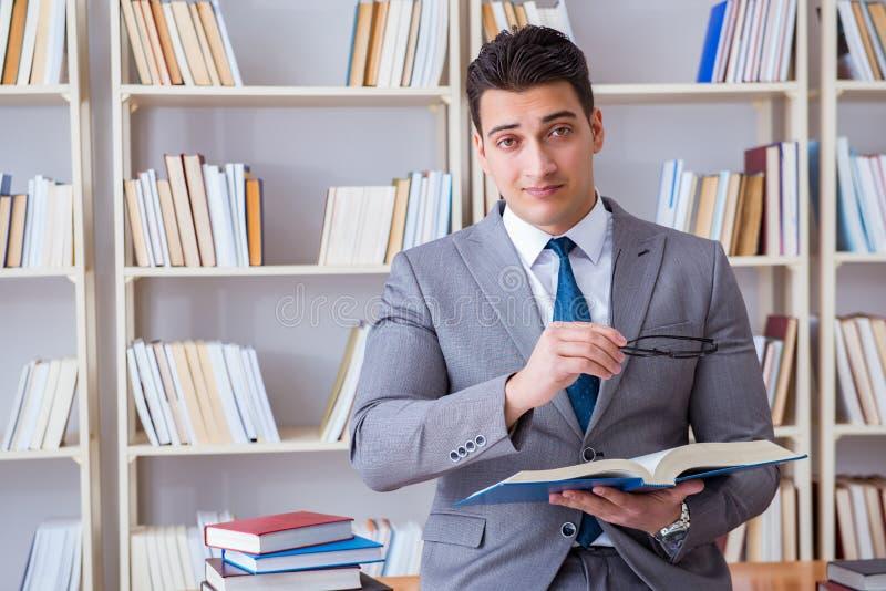 O estudo de trabalho do estudante de direitos comerciais na biblioteca foto de stock