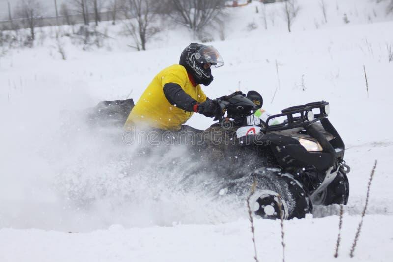O excitador da bicicleta do quadrilátero monta sobre a trilha da neve imagens de stock royalty free