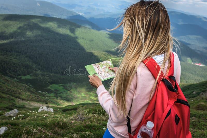 O excursionista com uma trouxa vermelha, explorador da mulher, veraneante perdeu nas expedições da montanha, viagem da campanha d fotos de stock royalty free