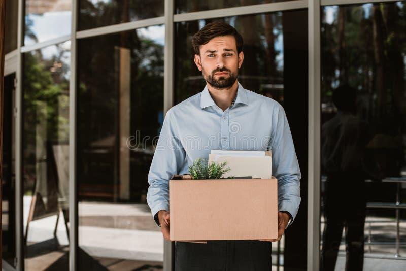 O executivo despedido triste está saindo do local de trabalho com o material imagem de stock