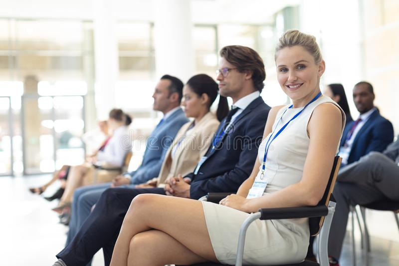 O executivo fêmea caucasiano novo sentou-se na sala de conferências, sorrindo à câmera imagem de stock