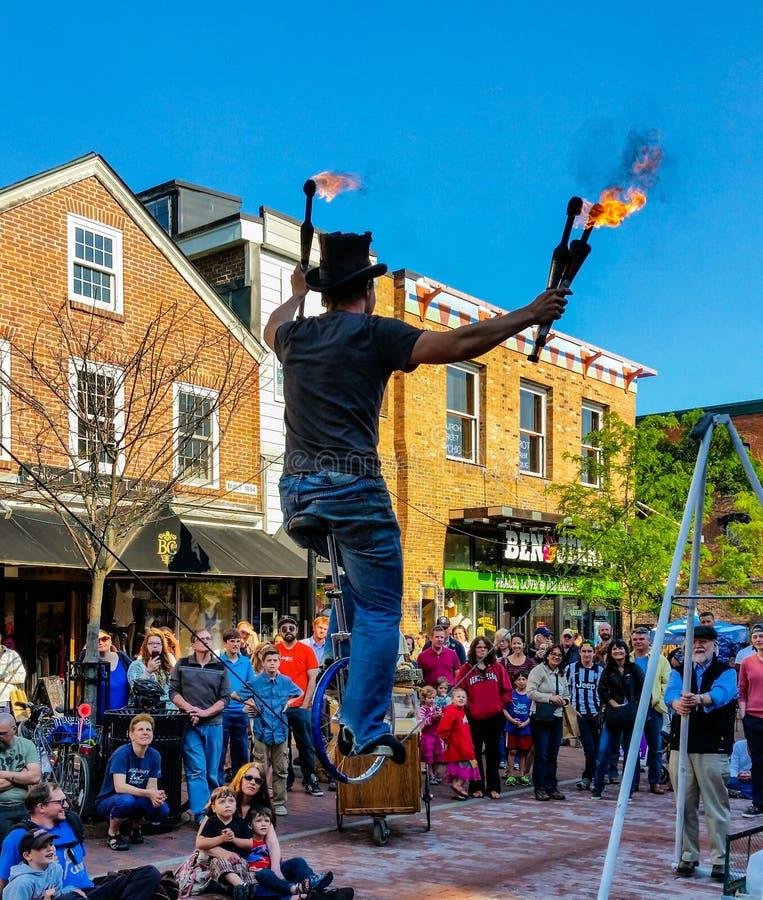 O executor da rua monta o unicyce no fio ao manipular varinhas do fogo imagens de stock royalty free