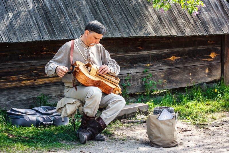O executor da rua no traje nacional ucraniano joga o órgão de tambor da mão (realejo, o violino da roda) fotografia de stock