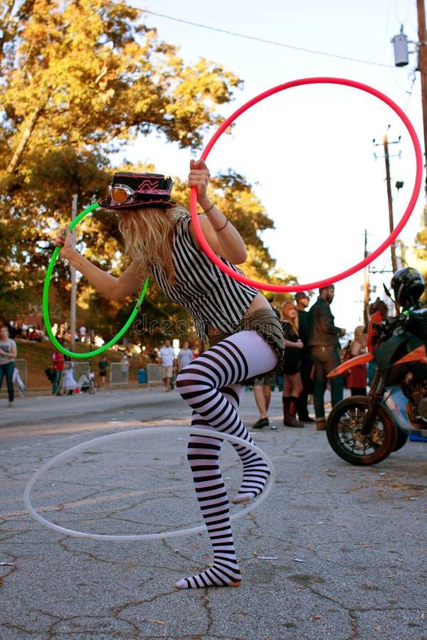 O executor fêmea da rua Entertains com as três aros de Hula fotos de stock