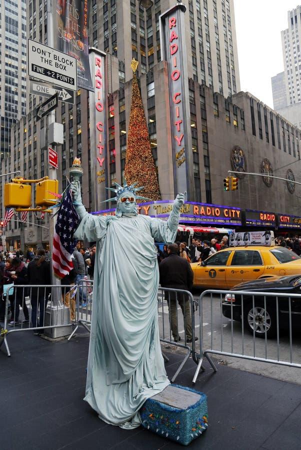 O executor não identificado da rua levanta como uma estátua da liberdade na parte dianteira do auditório da cidade do rádio do mar imagens de stock