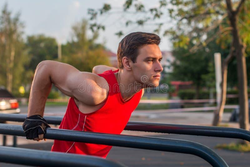 O exercício apto do homem para fora arma-se nas barras horizontais dos mergulhos que treinam o tríceps e fazer do bíceps empurra  fotografia de stock royalty free
