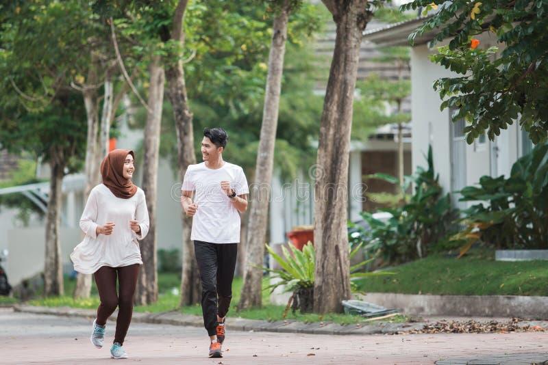 O exercício asiático novo feliz dos pares e aquece-se fotos de stock