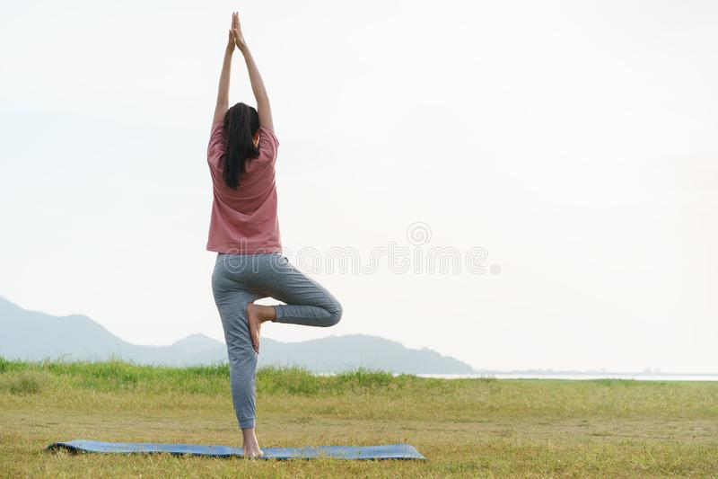 O exercício da jovem mulher e a ioga asiáticos da prática no relaxam o fundo da natureza fotos de stock royalty free