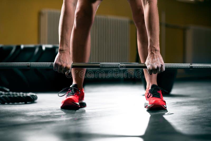 O exercício da mulher com o barbell no gym, prepara-se para levantar acima pesos fotografia de stock