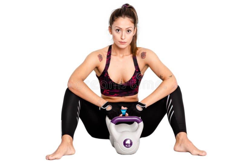 O exercício da mulher, quebra da aptidão relaxa após o exercício do kettlebell ou o assento cansado, estilo de vida saudável de f imagem de stock
