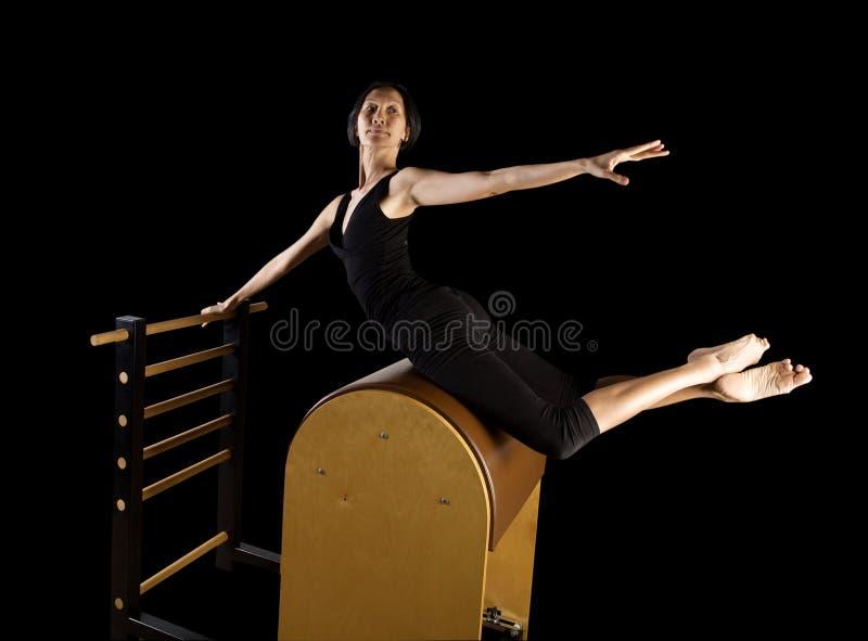 O exercício do reformista de Pilates exercita a mulher imagem de stock