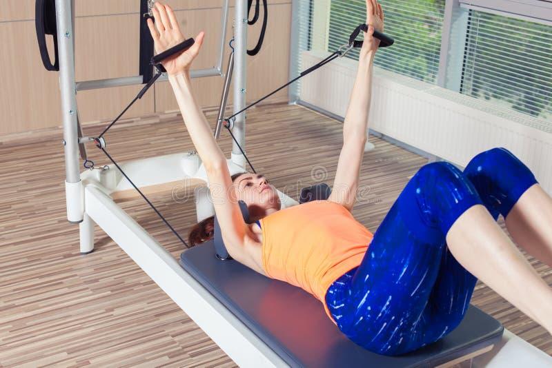 O exercício do reformista de Pilates exercita a mulher no gym interno fotos de stock