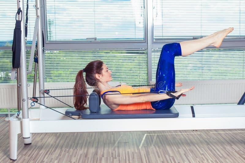 O exercício do reformista de Pilates exercita a mulher no gym interno imagens de stock royalty free