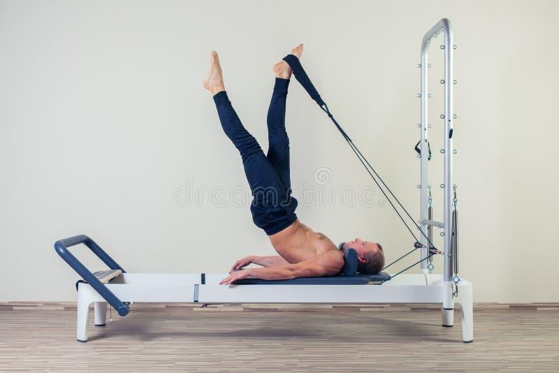 O exercício do reformista de Pilates exercita o homem no gym fotos de stock