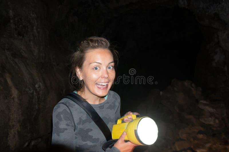 O explorador feliz da mulher guarda uma lanterna elétrica ao cavar e ao spelunking o subterrâneo em Lava Beds National Monument e foto de stock royalty free