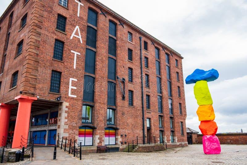 O exterior da galeria de arte de Tate Liverpool em Albert Dock Area em Liverpool, Merseyside, com uma escultura por Ugo Rondinone foto de stock