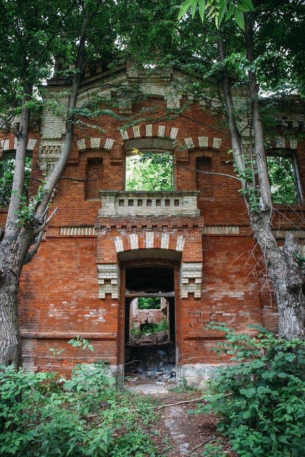 O exterior do tijolo antigo arruinado, abandonado envelheceu a construção do castelo coberto de vegetação com a grama e as planta imagens de stock royalty free