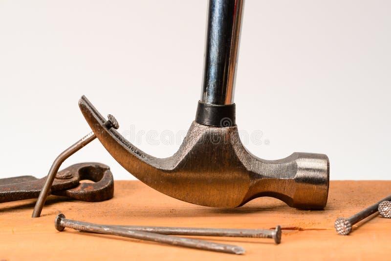 O extrator de prego do martelo do vintage puxa prego grande curvado fora da placa, com as quelas e os pregos forjados sujos do vi imagem de stock
