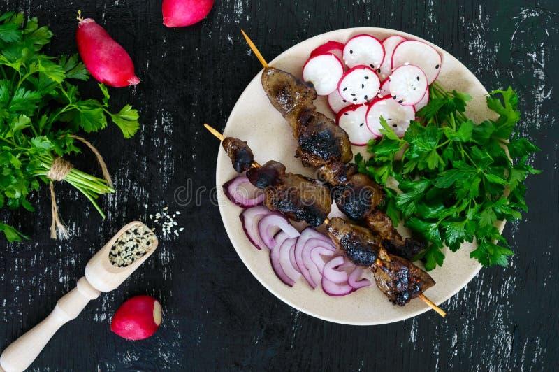 O fígado do coelho roasted em espetos e em salada do rabanete imagens de stock