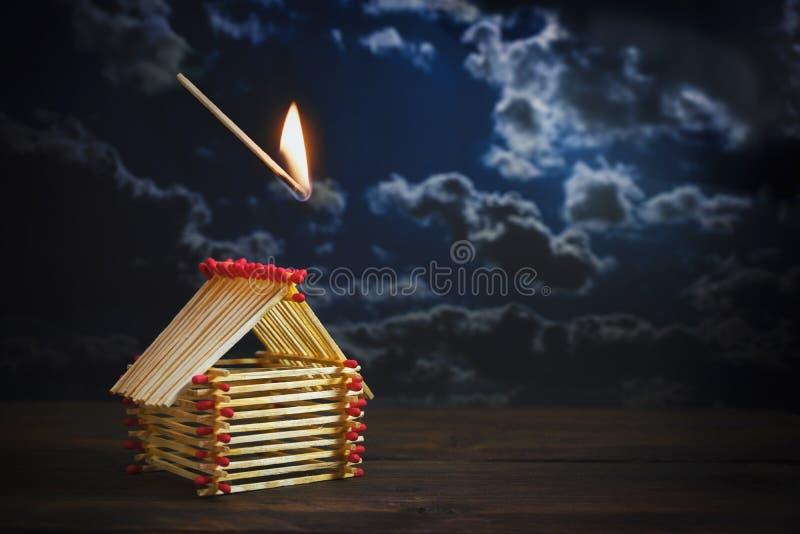 O fósforo inflamado está caindo em uma casa construída dos fósforos contra um céu tormentoso escuro com espaço da cópia, conceito fotos de stock royalty free
