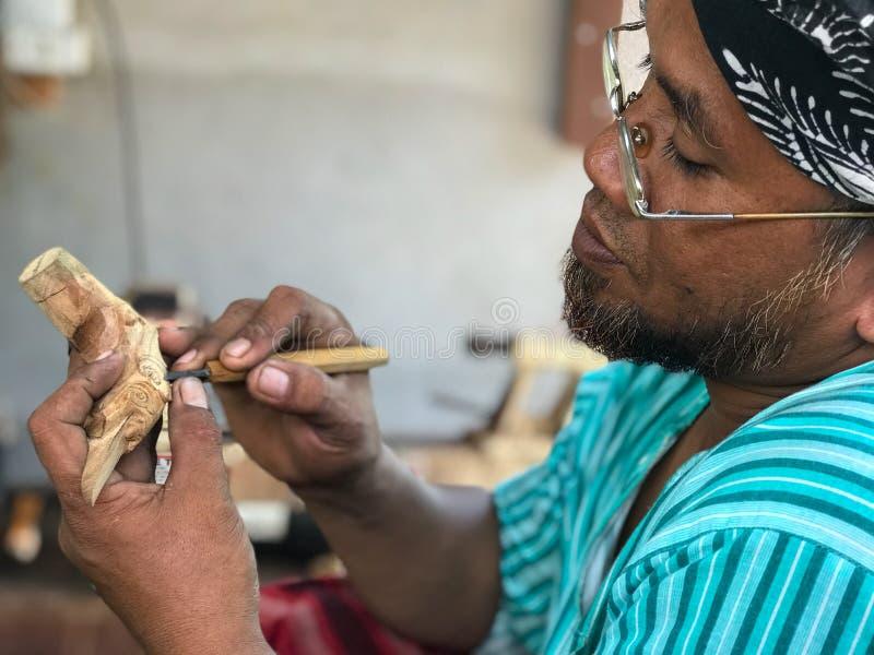 O fabricante não identificado dos keris cinzela o punho de madeira dos keris imagens de stock royalty free