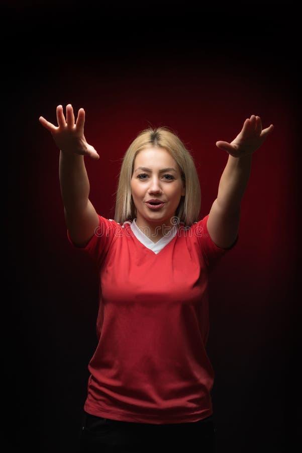 O fan de futebol bonito louro da mulher que chanting com ambos os braços aumentou na camisa vermelha de T foto de stock