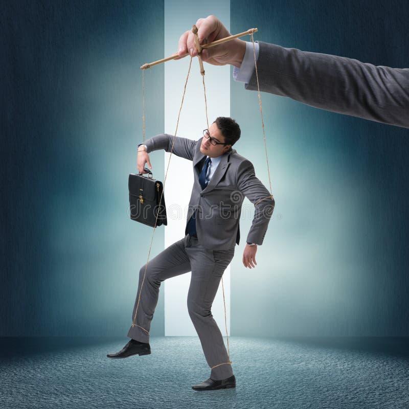 O fantoche do homem de negócios que está sendo manipulado pelo chefe imagens de stock royalty free