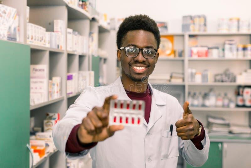 O farmacêutico afro-americano de sorriso novo do homem que guarda comprimidos vermelhos empola à disposição ao estar no interior  fotos de stock