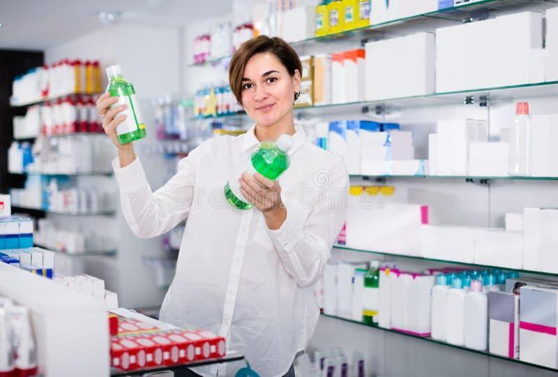 O farmacêutico está mostrando produtos do cuidado do corpo foto de stock