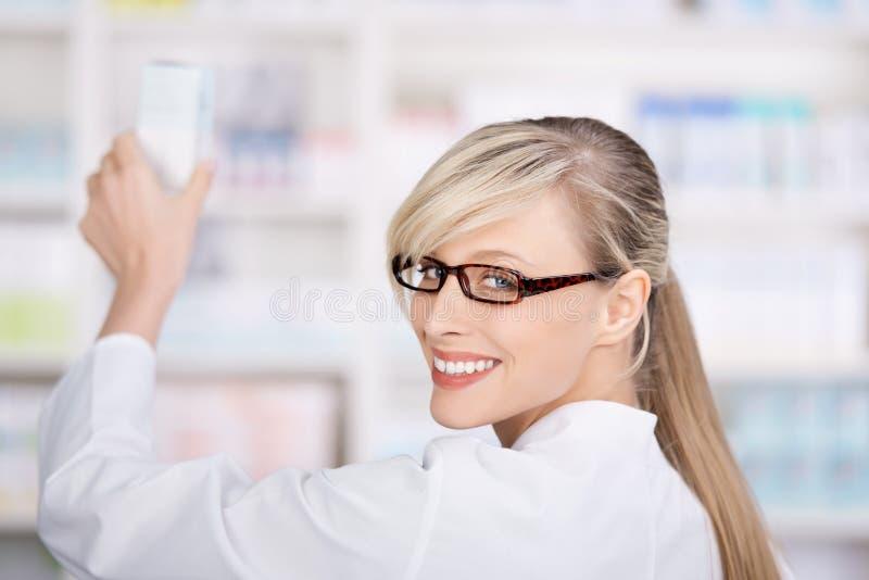 O farmacêutico fêmea amigável armazena as medicinas fotografia de stock royalty free