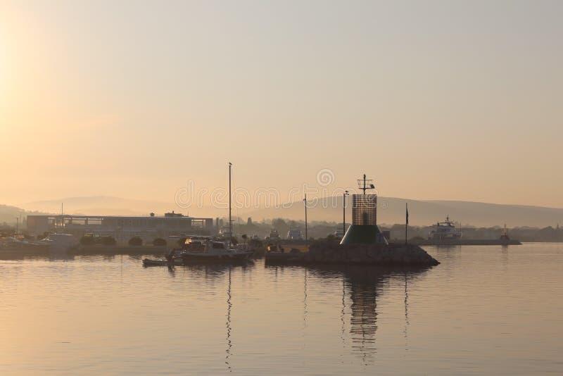 O farol é ficado situado na entrada ao porto de uma cidade mediterrânea nos raios do sol de aumentação Humor romântico E fotografia de stock