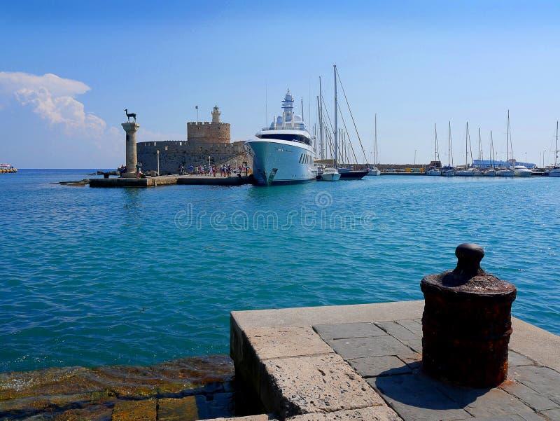 O farol e a fortaleza de St Nikolas que guardou a entrada ao porto de Mandracki na ilha do Rodes fotografia de stock