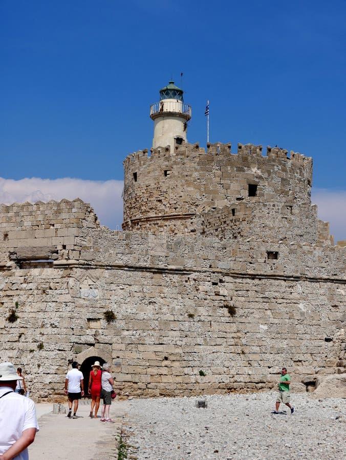 O farol e a fortaleza de St Nikolas que guardou a entrada ao porto de Mandracki na ilha do Rodes imagem de stock royalty free