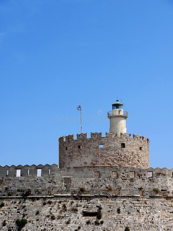 O farol e a fortaleza de St Nikolas que guardou a entrada ao porto de Mandracki na ilha do Rodes fotos de stock royalty free