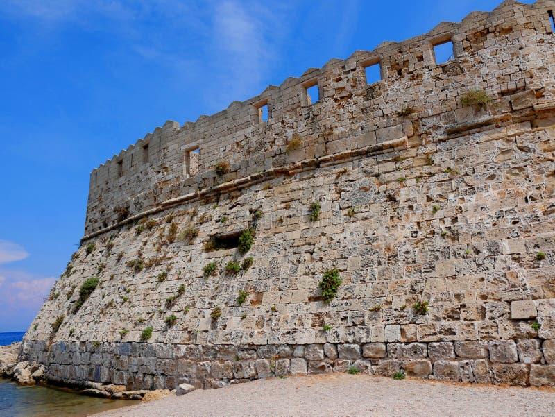 O farol e a fortaleza de St Nikolas que guardou a entrada ao porto de Mandracki na ilha do Rodes fotografia de stock royalty free
