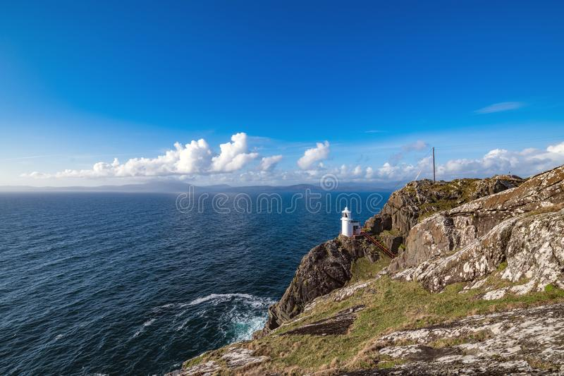 O farol principal do carneiro na extremidade da península principal do carneiro na Irlanda imagem de stock