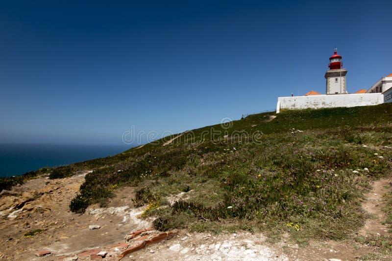 O farol westernmost de Cabo a Dinamarca Roca em Porugalia com o crescimento amarelo-florescido do figo hotentote fotos de stock