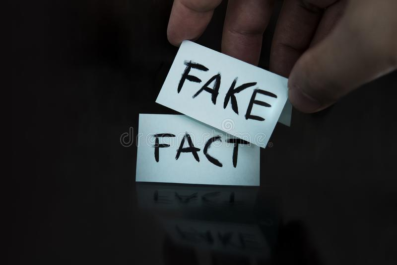 O fato é substituído por uma falsificação substituição de conceitos um homem muda os sinais com as palavras fato em falso em pret imagens de stock royalty free