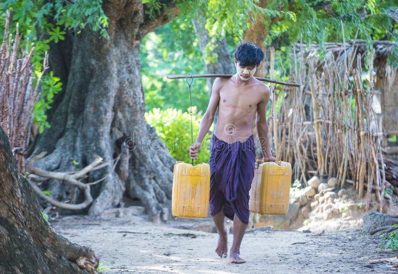O fazendeiro burmese que leva cubetas plásticas encheu-se com água imagens de stock