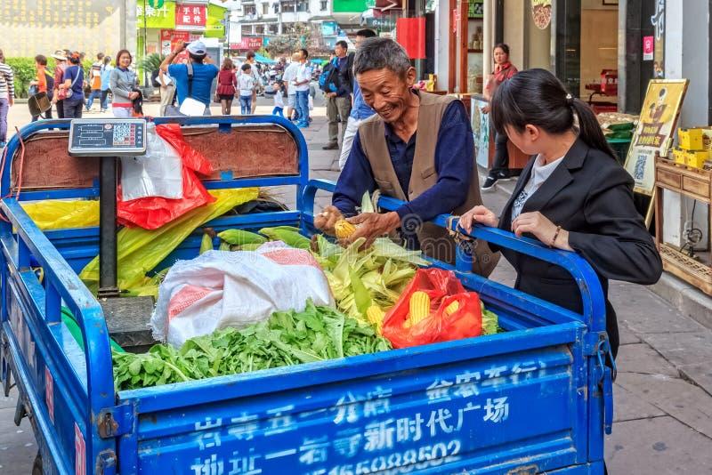 O fazendeiro chinês idoso vende o milho e vegetais frescos em China imagens de stock royalty free