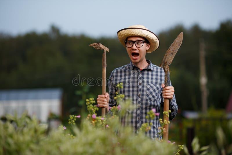 O fazendeiro com pá e o ancinho que gritam na exploração agrícola trabalham foto de stock royalty free