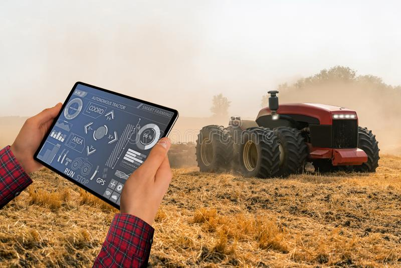 O fazendeiro controla um trator autônomo imagem de stock
