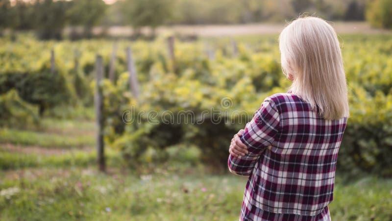 O fazendeiro da jovem mulher olha seu jardim ou vinhedo imagem de stock