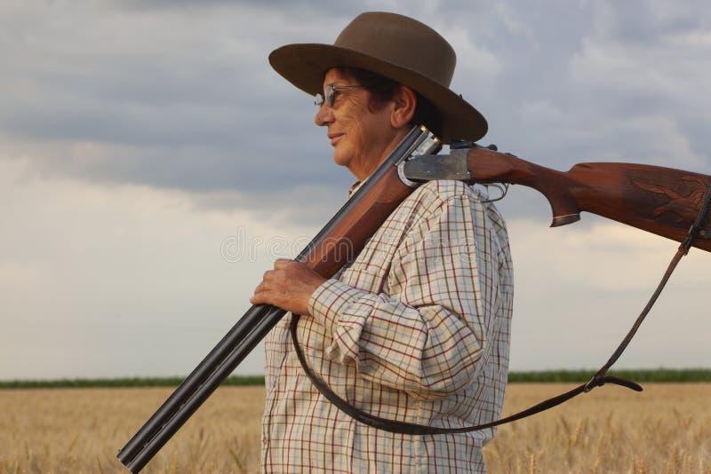 O fazendeiro do ` s da senhora com um chapéu mantém seu shootgun em sua mão imagem de stock royalty free