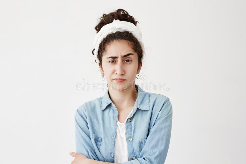 O fazer-pano vestindo da menina infeliz séria no cabelo escuro ondulado tem expressão atraente da cara, olha de sobrancelhas fran foto de stock royalty free