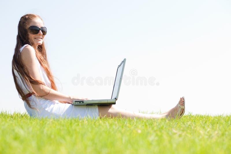 O feamle novo senta-se no parque e em usar um portátil fotos de stock