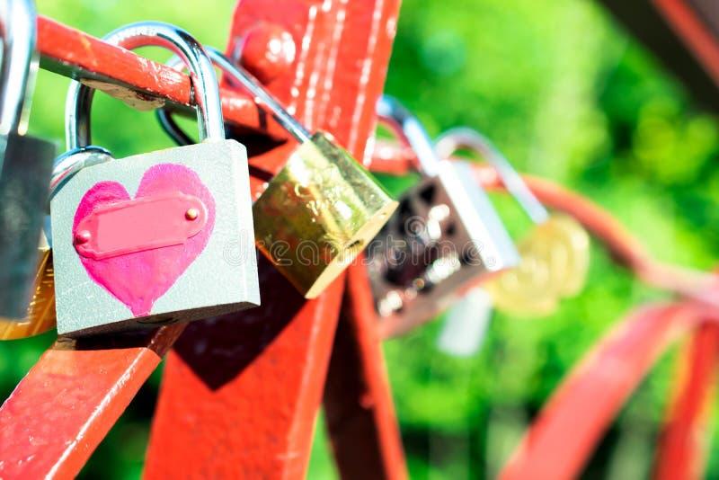 O fechamento com um coração pintado nele é fixado nos trilhos da ponte que simboliza o romance e o amor fotografia de stock
