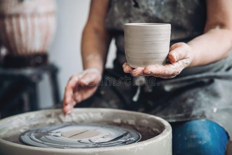 O feiticeiro enrugado das mãos na roda de oleiro faz pratos da argila Lugar a trabalhar imagens de stock
