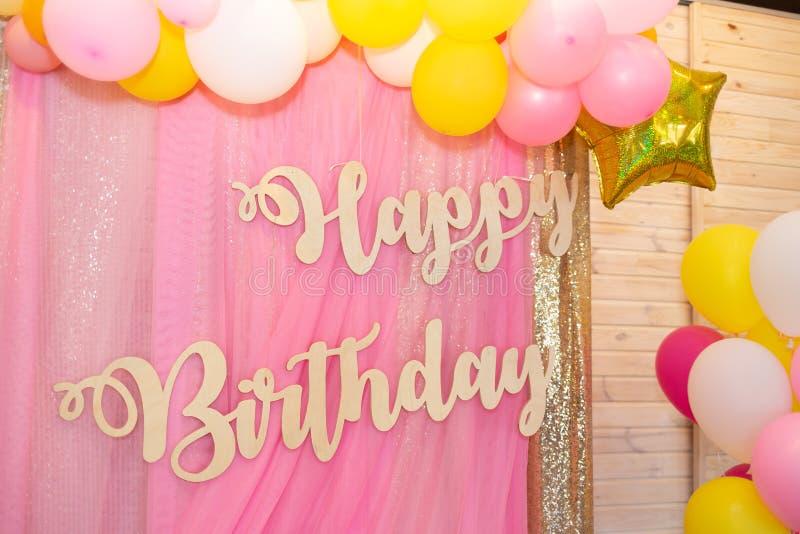 O feliz aniversario da inscrição feito da madeira clara em um rosa macio foto de stock royalty free